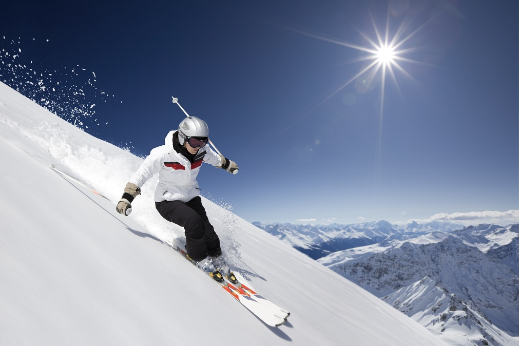 female skier skiing downhill with sun and mountains.